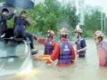 雨中两人被困车顶 消防人员蹚水救人